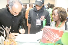 KISSF-Chairman-Aasif-Karim-autographs-his-book-The-Karims-as-KISFF-Brand-Ambassadors-Douglas-Wakiihuri-and-Rose-Tata-Muya-look-on