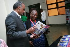 Aasif-Karim-and-Occidental-insurance-general-manager-Agatha-Solitei-peruse-the-sports-monthly-magazine
